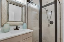 3rd floor hall bath with quartz vanity and travertine shower.