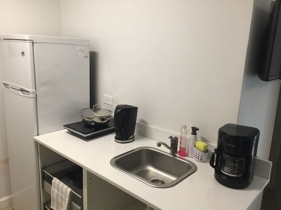 Small kitchen with all essentials. Microwave, refrigerator, cooktop, coffee maker and more!