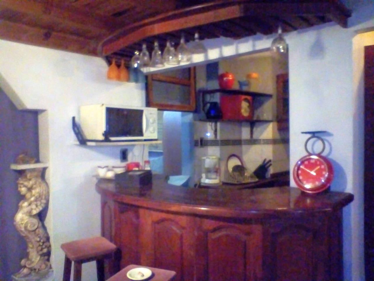 la barra separa la cocina de la mesa comedor, con dos taburetes , y un cuelga-copas , microondas , cafetera eléctrica y tostadora