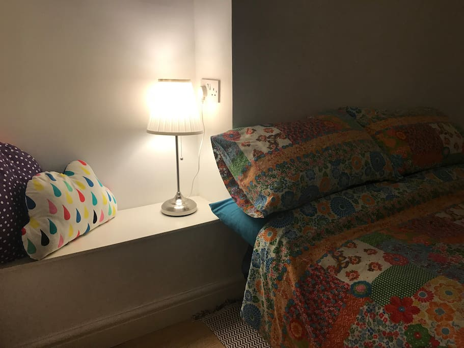 There is a lamp and power-outlet next to the bed.