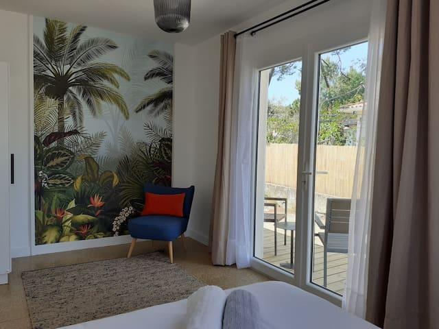 La chambre de la suite et sa petite terrasse en bois.