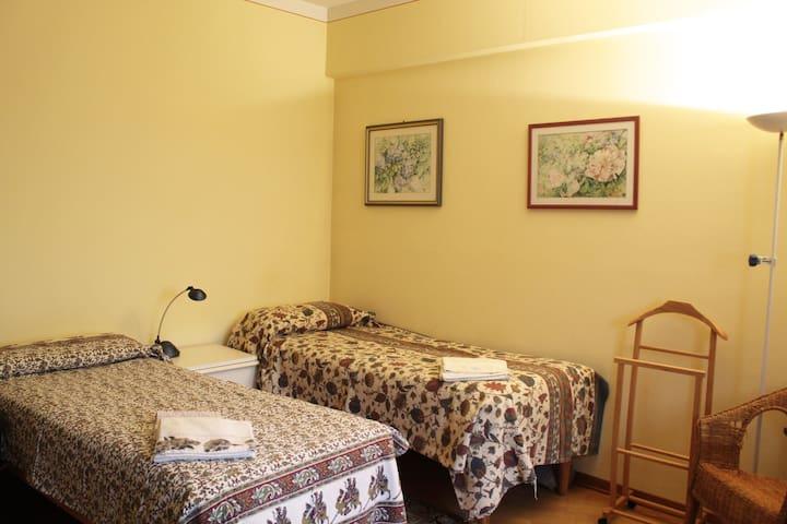 Ampia camera con due letti singoli, armadio, tavolo e poltrona