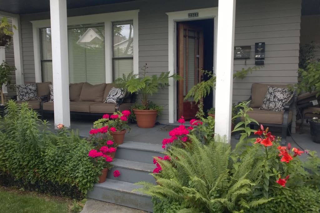 Covered front porch. With outdoor couch and two reading chairs