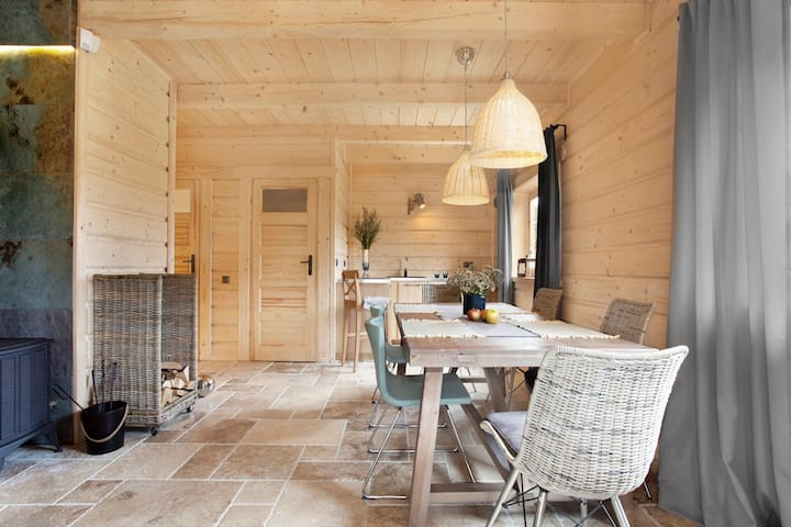 Domy z kominkami do wynajęcia w Sasinie posiadają na parterze komfortową głęboką sofę, jak i znajdą Państwo tu duży stół obiadowy