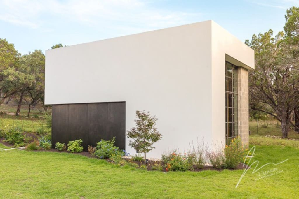 Steel panels and pure white stucco adorn this hill country studio loft.