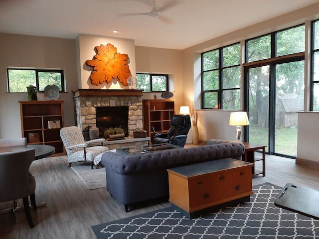 Comfortable living area with lots of windows!  Table for two by window, sofa & massage chair.