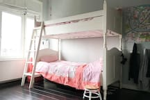 Bedroom with a bunk bed and a crib.