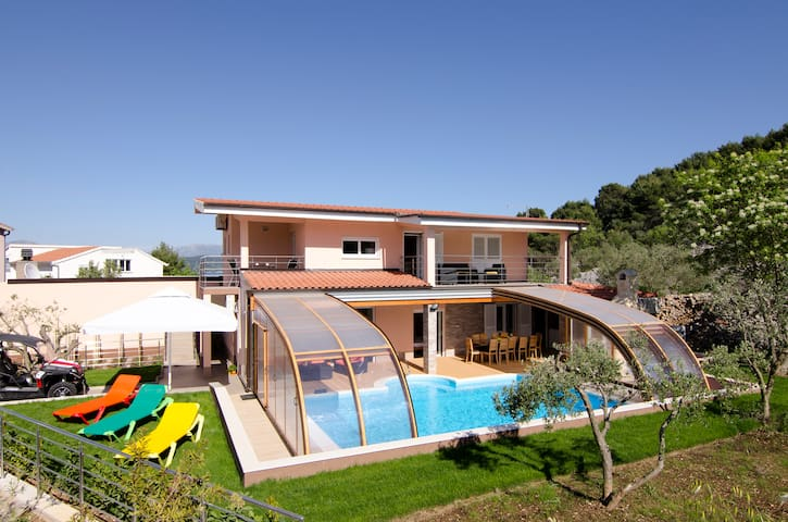 Villa with an open swimming pool shade
