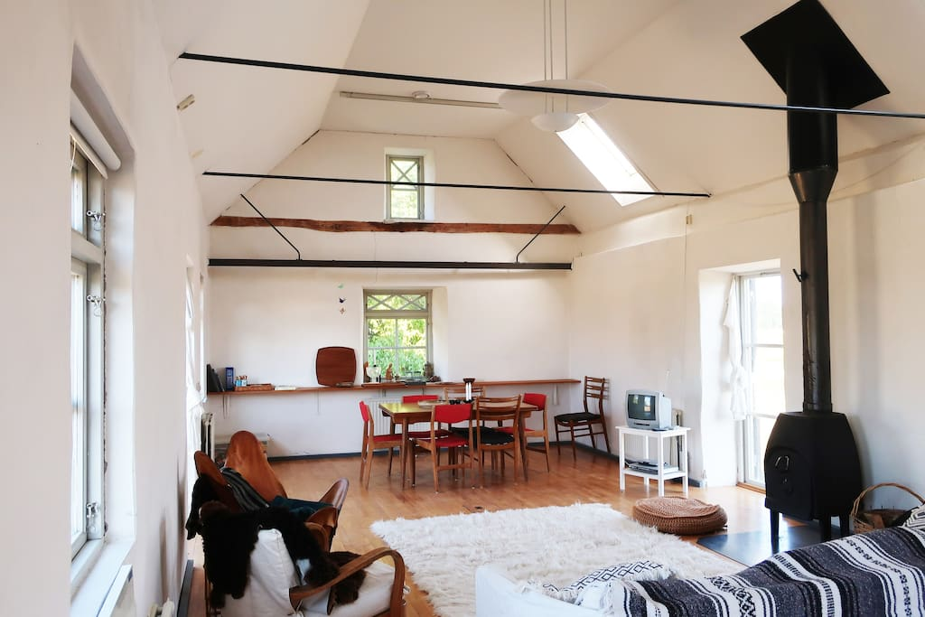 Living room with plenty of natural light and cast iron stove