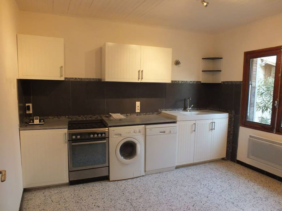 Kitchen with washing machine, dish washer, cooker and authentic stone sink
