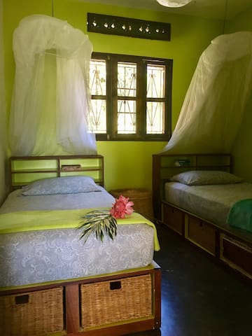 Twin room with large circular mosquito nets, under-bed storage and bookshelf. Very comfortable good quality sprung mattresses.