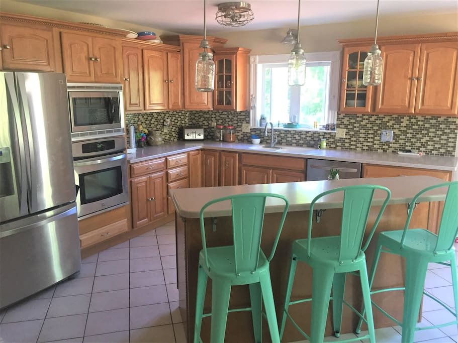 Big, open kitchen, double sink, high counter, three stools.