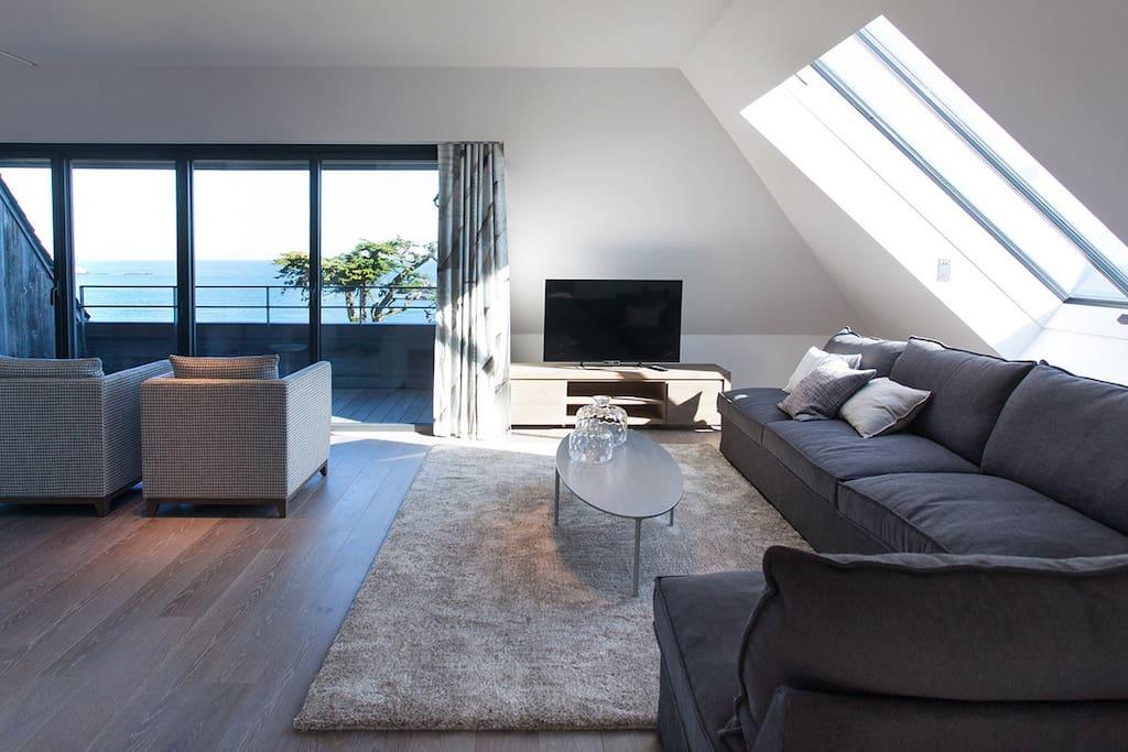 Salon/séjour ouvert sur un balcon privé vue sur mer