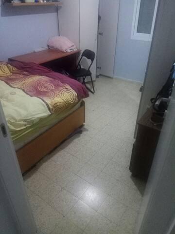 חדר שינה עם מיטה זוגית ומזגן בשכונה קרובה לפסטיבל