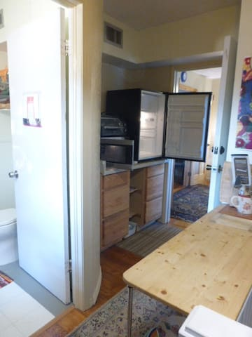 Sitting room view of hall kitchenette with refrigerator, microwave, toaster oven, etc.