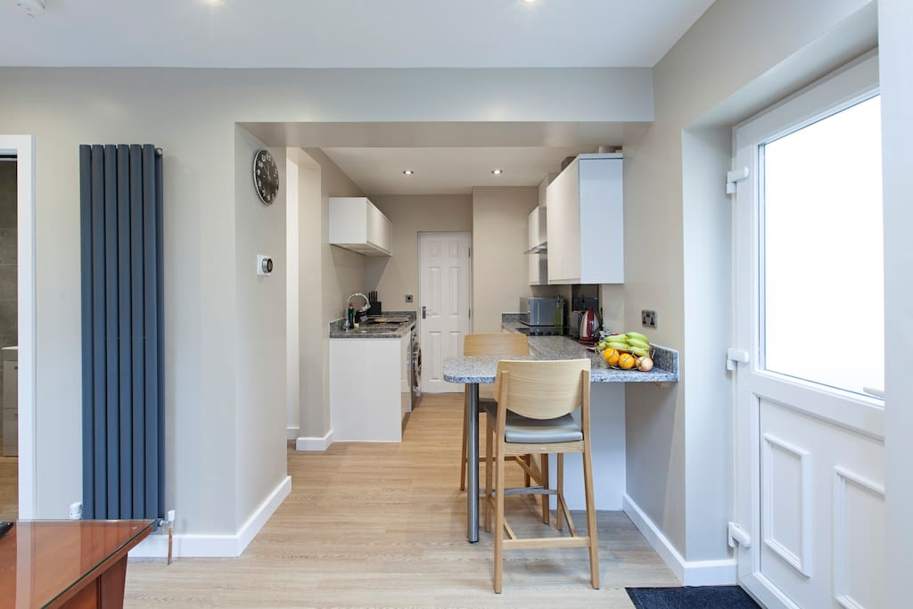 Breakfast bar and open kitchen with washing machine and dryer, fridge freezer