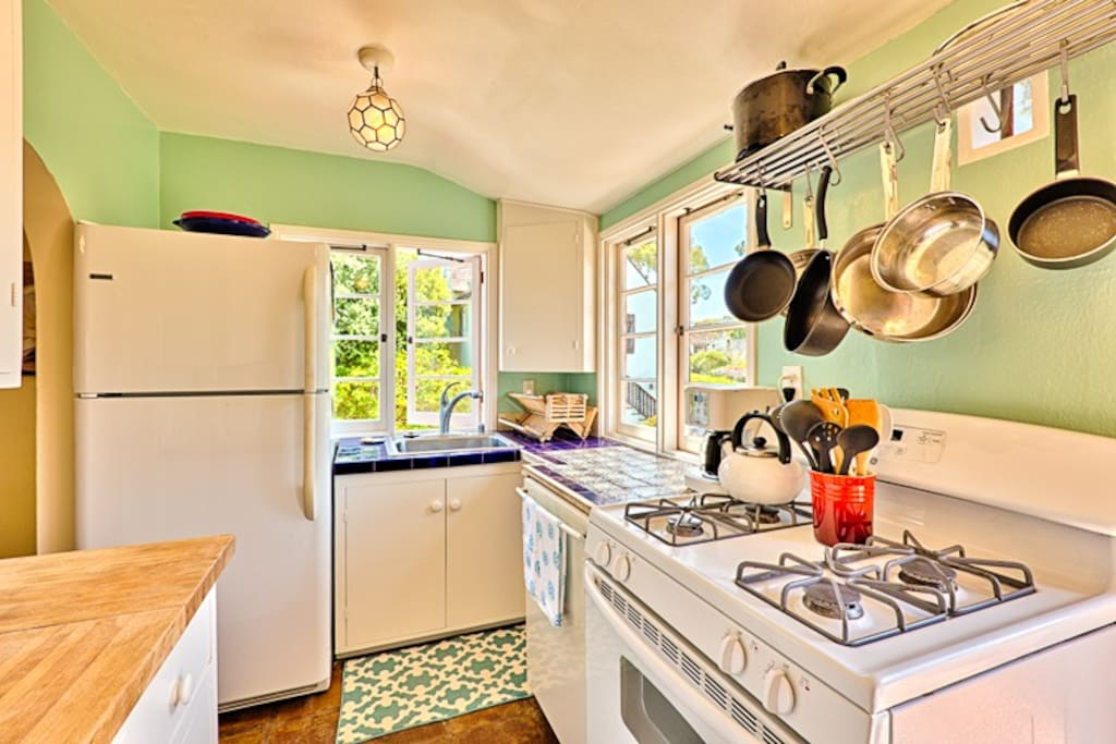 Sunny and cute kitchen has gas range and is fully equipped with all of your culinary needs