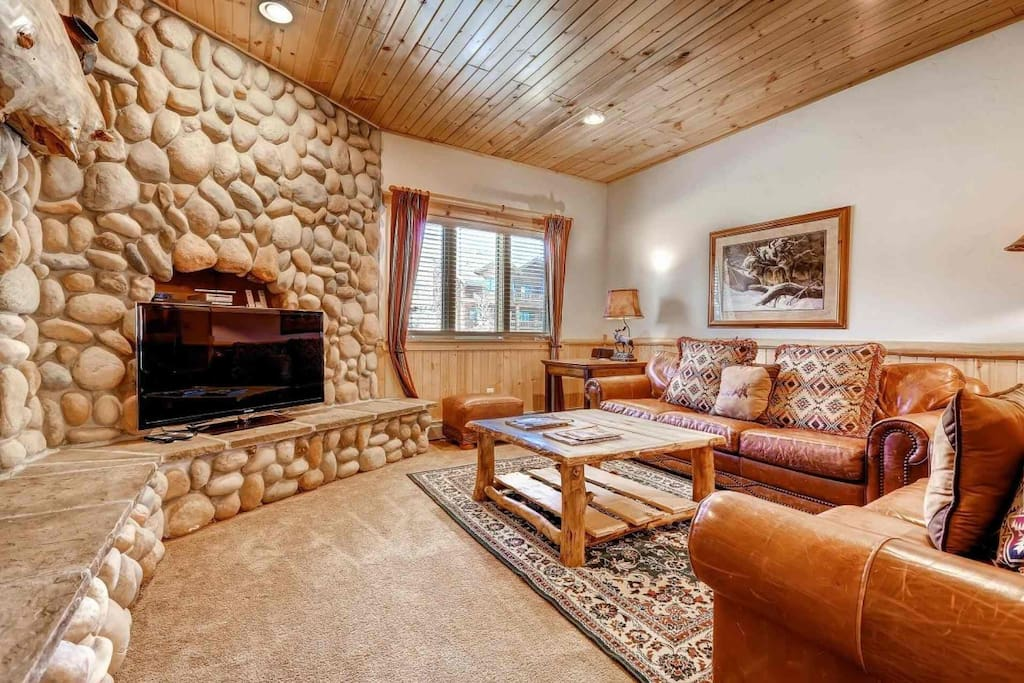 "Living area offers a large 48"" HDTV, comfortable high end leather furniture, mountain decor and detailing and a floor to ceiling river rock fireplace."