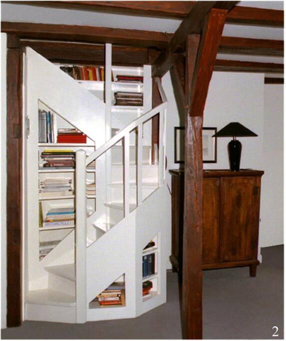 Diese in einer Bücherwand eingebaute Treppe führt zur offenen Schlafgalerie oberhalb des Wohnraumes. Ein zusätzliches Ankleidezimmer ergänzt den offenen Raum.