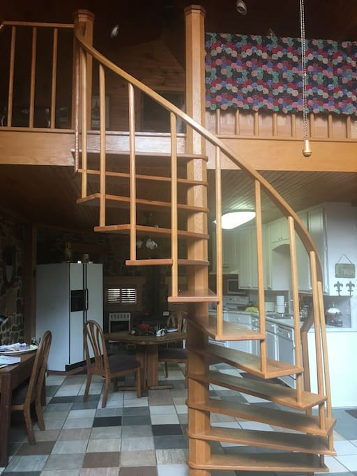 The hand crafted oak spiral staircase separates the living area from the dining/kitchen area  while maintaining an open concept.