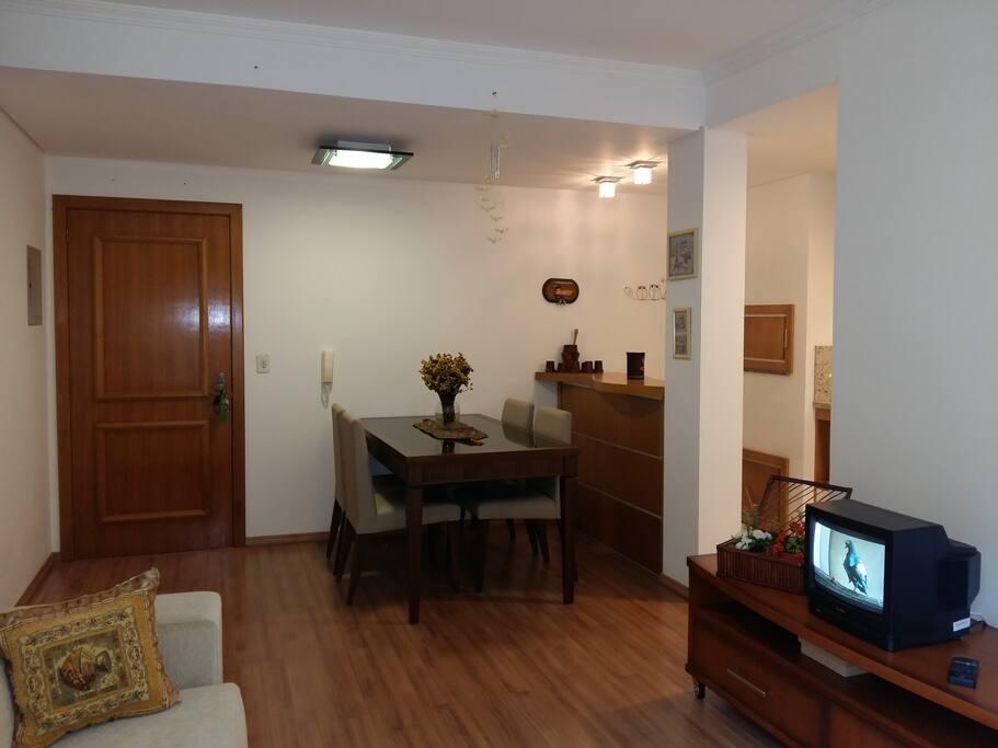 Sala de estar com televisão e sala de jantar para 04 pessoas.