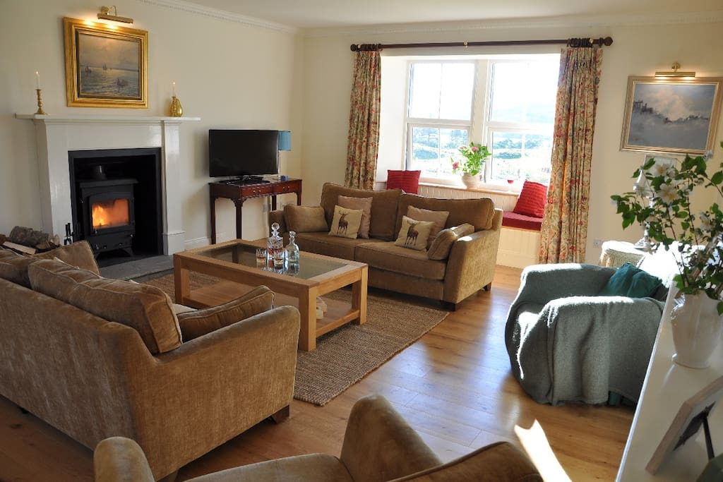 Large sitting room with log burner and smart TV.