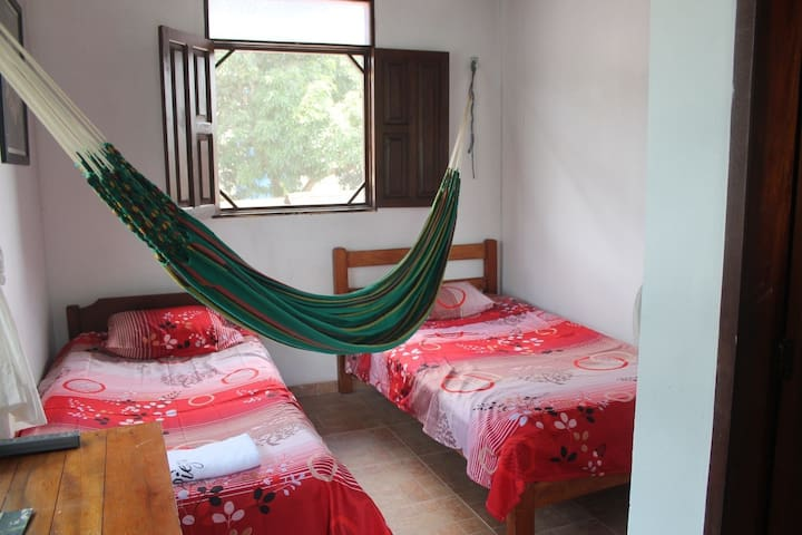 Room with two beds and hammock. Also has two windows