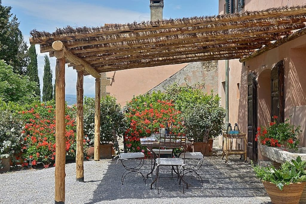 Outdoor dining area under pergola surrounded by lovely garden