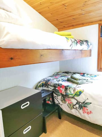The bunk room has two twin-size beds and a closet with hanging space.
