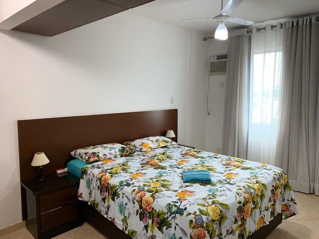 Quarto 01 Cama Queen, ar condicionado, 2 criadinhos, um guarda roupas com porta de espelho, sapateira e armários.