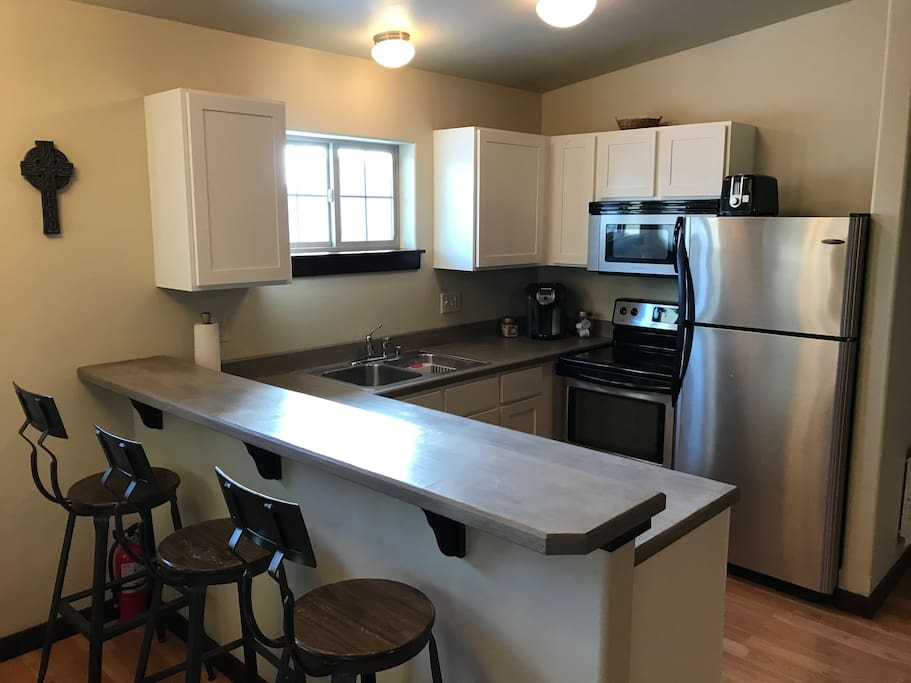 Kitchen is fully stocked for short or long term stays. Concrete counters, modern white cabinets and stainless appliances make this perfect 1 BR apt feel like home.
