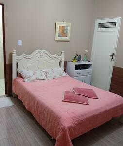 Suite simples com cama de casal ao fundo da casa.