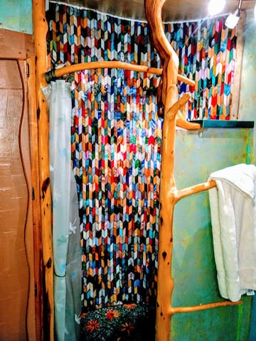 This shower was handcrafted by a local artist. The stain glass was individually placed with love and care. The shower rod and towel rack have also been crafted from trees off our property.