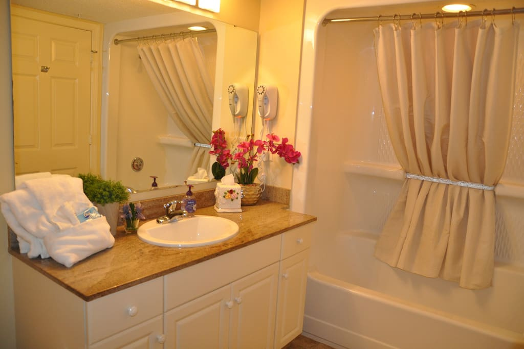 Elegant granite top vanity in the full bathroom, equipped with a built-in hairdryer and extra thick and fluffy towels