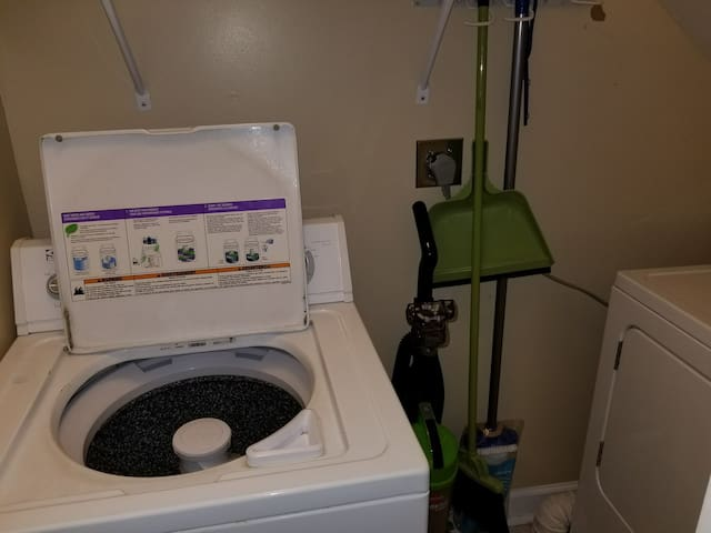 Full size washer located in laundry area under stairway.