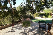 In the foreground, a swing in the shade of the old carob tree.In the background the gazebo and table tennis table