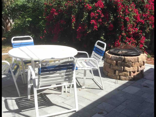The backyard has a table and chairs to enjoy while cooking on the grill. There is a new 10' umbrella for shade and a fire pit for s'mores!!