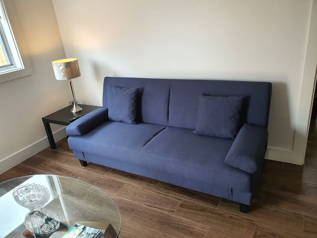 Living room with sofa bed and coffee table.  Note: Linen for sofa bed is available on request at no extra cost.