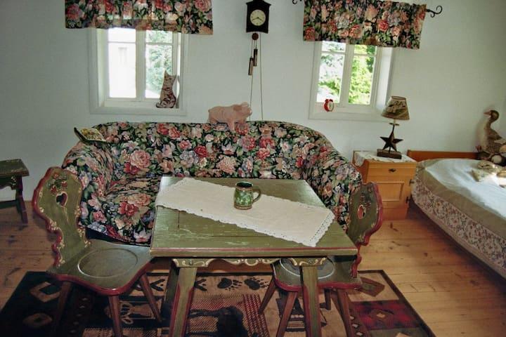 Sofa mit Tisch und Sicht auf das zusätzliche Bett