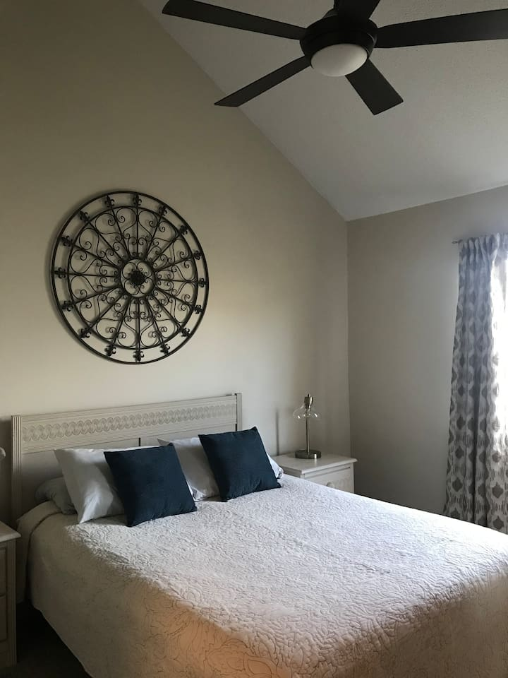 Queen bed with vaulted ceiling and fan.