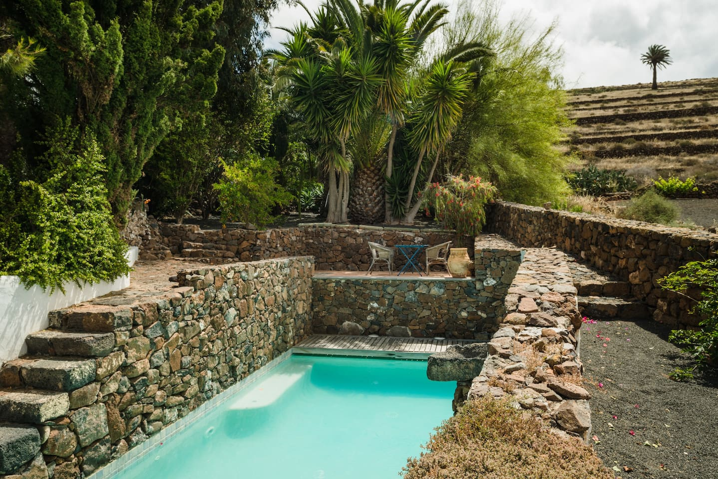 The villa features a private heated pool framed by a lush garden and typical rough stone walls