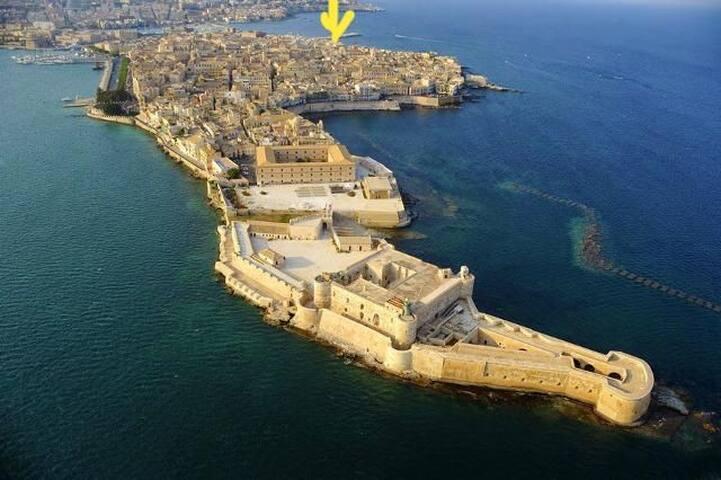 Questa foto mostra la veduta aerea dell ' isola di Ortigia , così chiamata perché, dall' alto , sembra una quaglia allungata in volo. La freccia gialla indica l'ubicazione del caseggiato dove è sito l'appartamento.