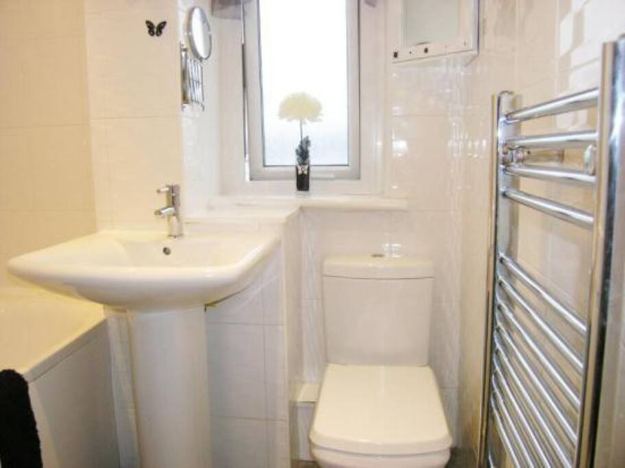 Bathroom with bath, shower and heated towel rail