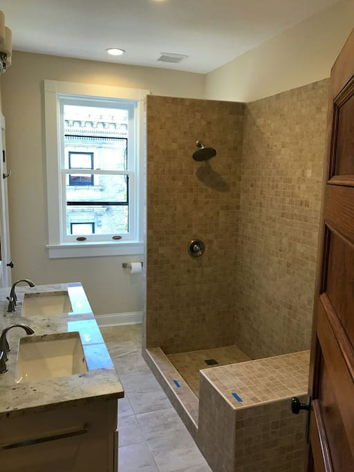 This shows the bathroom just before the shower doors were installed.  Full-sized washer and dryer tucked behind the door.