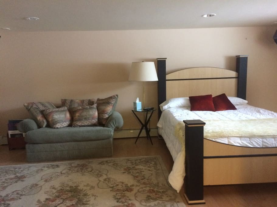 Cozy guest room features a queen bed and twin sofa-bed, dresser and office desk.
