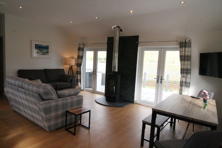 Beautiful open plan living area with wood burning stove, double patio doors onto the decking and gorgeous views over the loch