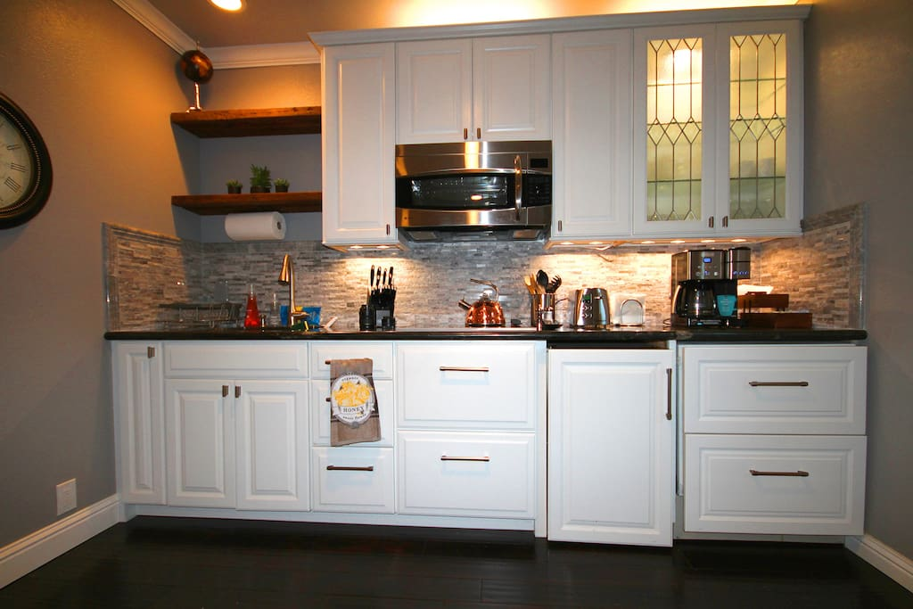 Full kitchen with electric range, microwave/convection oven, and under-counter fridge and freezer.
