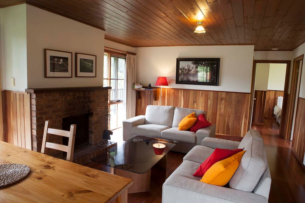 Living and dining area with wood fire, looks out onto balcony with views of forest
