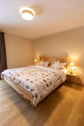 Schlafzimmer mit Doppelbett aus Buchenholz sowie Zugang zum Balkon mit Blick auf die Berge