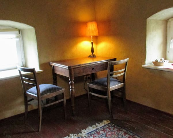 Wir haben einen kleinen Schreibtisch und zwei Stühle in Zimmer gestellt. Die passen hier perfekt in die Ecke. Der Schein trügt nicht - das Zimmer ist durch die kleinen Fenster dunkel. Im Sommer schläft man dort, im Winter ist es gemütlich.